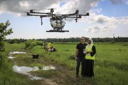 In this photo taken Thursday, Oct. 31, 2019, Eduardo Rodriguez, left, of drone manufacturer DJI, trains Khadija Ali Abdulla, right, from the State University of Zanzibar, how to fly a drone to spray the breeding grounds of malaria-carrying mosquitoes, at Cheju paddy farms in the southern Cheju region of the island of Zanzibar, Tanzania