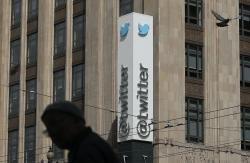 In this July 9, 2019, file photo a pedestrian walks across the street from the Twitter office building in San Francisco