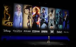 Characters from Disney and Fox movies are displayed behind Cathleen Taff, president of distribution, franchise management, business and audience insight for Walt Disney Studios during the Walt Disney Studios Motion Pictures presentation at CinemaCon 2019.