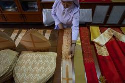 Sister Sukanya Sukchai adjusts a newly made ceremonial garments at a Catholic preparatory school in Bangkok, Thailand.