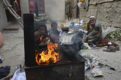 In this Oct. 29, 2019 photo, Yousuf, who fled with his family from his home in eastern Afghanistan eight years ago to escape the war, sits with children while his wife burns plastic as she makes tea, in Kabul, Afghanistan