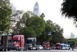 In this Friday, Nov. 13, 2009 file photo a caravan of trucks from the ports of Los Angeles and Long Beach, Calif., drive around Los Angeles City Hall during a protest against container fees being assessed against independent truckers