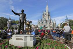 Guests watch a show near a statue of Walt Disney and Micky Mouse in front of the Cinderella Castle at the Magic Kingdom at Walt Disney World in Lake Buena Vista, Fla.