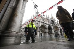 A city worker stop tourists entering a flooded St.Mark square in Venice, Italy, Sunday, Nov. 17, 2019.