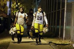 Camden High School football players walk down Park Blvd. in Camden, N.J., as they head back to their football field and locker room on Friday night, November 15, 2019.