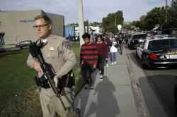 This Nov. 14, 2019, file photo shows students being escorted out of Saugus High School after reports of a shooting in Santa Clarita, Calif.