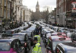 In this Wednesday, Feb. 10, 2016 file photo, London taxis block the roads during a protest in central London, concerned with unfair competition from services such as Uber