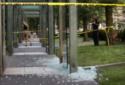 This Aug. 14, 2017 file photo shows broken glass on the ground near police tape at the New England Holocaust Memorial in Boston