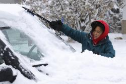 Meg Jones cleans the snow off her car outside her house on 2nd Avenue in Scottsbluff, Neb.