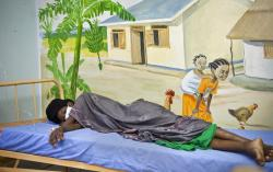 a newly-diagnosed HIV positive woman, who arrived at the hospital with symptoms of tuberculosis (TB), lies in the treatment ward of the Mildmay Uganda clinic