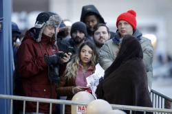 People wait in the cold outside a Best Buy store for it to open for a Black Friday sale.