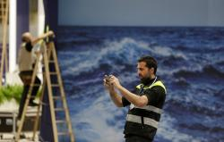 A worker takes a photograph while stands are being set up for the COP25 Climate summit in Madrid, Spain, Sunday, Dec. 1, 2019