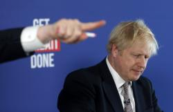 Chancellor of the Duchy of Lancaster Michael Gove, left, gestures during a media conference with Britain's Prime Minister Boris Johnson, right, in London, Friday, Nov. 29, 2019. Britain goes to the polls on Dec. 12