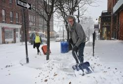 Zach Lusignan of Ryan's Landscaping shovels the snow on Spring Street in Williamstown, Mass.