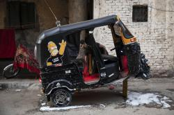 In this Nov. 19, 2019 photo, a tuk-tuk driver washes his vehicle in an alleyway of a slum in Cairo, Egypt