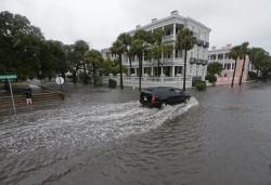 In this Oct. 3, 2015, file photo, a driver takes his truck through a flooded street in Charleston, S.C.