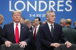 In this Dec. 4, 2019, photo, U.S. President Donald Trump and NATO Secretary General Jens Stoltenberg wait to take their seats prior to a NATO leaders meeting at The Grove hotel and resort in Watford, Hertfordshire, England