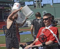 Boston Red Sox player Mike Napoli takes part in the re-launch of the Ice Bucket Challenge as former Boston College baseball player Pete Frates, right, looks on at Fenway Park in Boston.