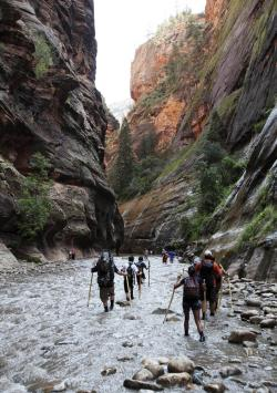 """In this Sept., 5, 2009, file photo, hikers wade through the cold Virgin River along the """"Narrows,"""" in Zion National Park, Utah"""
