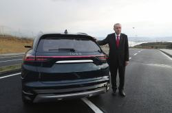 Turkish President Recep Tayyip Erdogan poses with a prototype of a domestically produced electric car, in Gebze, Turkey, Friday, Dec. 27, 2019