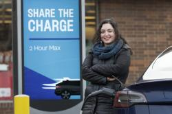 In this Friday, Dec. 20, 2019, photo, Neda Deylami poses for a portrait while charging her electric vehicle at a Chicago area grocery store