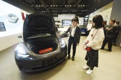 In this Nov. 24, 2019, photo, a saleswoman talks about a Tesla Model 3 car at a Tesla showroom in Hangzhou in eastern China's Zhejiang Province
