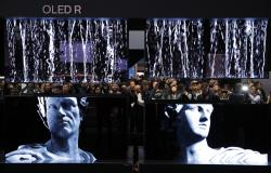 People take pictures of a display of LG Signature OLED R TVs at the LG booth during the CES tech show, Tuesday, Jan. 7, 2020, in Las Vegas.