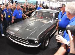 "People surround the original 1968 ""Bullitt"" Mustang GT Friday, Jan. 10, 2020 in Kissimmee, Fla."