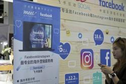 In this April 28, 2017, file photo, a foreign social media advertisement like Facebook and Instagram promotes its services during the Global Mobile Internet Conference (GMIC) in Beijing, China