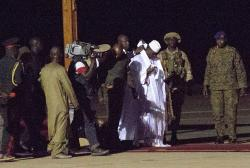 Gambia's defeated leader Yahya Jammeh, wearing white, departs at Banjul airport.