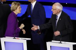Democratic presidential candidate Sen. Elizabeth Warren, D-Mass., left and Sen. Bernie Sanders, I-Vt. talk Tuesday, Jan. 14, 2020, after a Democratic presidential primary debate hosted by CNN and the Des Moines Register in Des Moines, Iowa.