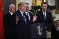 """President Donald Trump, gestures, as Vice President Mike Pence, back left, Secretary of Treasury, Steven Mnuchin, back center, and U.S. Trade Representative Robert Lighthizer, right, listen during a signing ceremony of the """"phase one"""" of a US China trade agreement, in the East Room of the White House, Wednesday, Jan. 15, 2020, in Washington"""