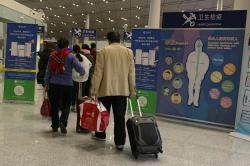 In this Jan. 13, 2020, photo, travelers pass by a health checkpoint before entering immigration at the international airport in Beijing.