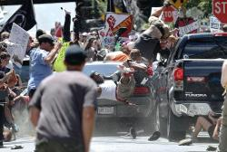 In this Aug. 12, 2017 file photo, people fly into the air as a vehicle drives into a group of protesters demonstrating against a white nationalist rally in Charlottesville, Va.