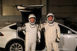 In this Friday, Jan. 17, 2020, photo provided by NASA, astronauts Doug Hurley, left, and Robert Behnken pose in front of a Tesla Model X at a SpaceX launch dress rehearsal, at Kennedy Space Center, in Florida