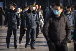 A security officer wears a face mask as he patrols outside of the Beijing Railway Station in Beijing, Monday, Jan. 20, 2020.