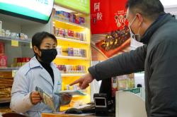 Staff sell masks at a Yifeng Pharmacy in Wuhan, China.