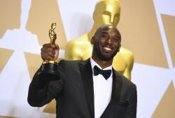 """This March 4, 2018 file photo shows Kobe Bryant, winner of the award for best animated short for """"Dear Basketball"""", at the Oscars in Los Angeles."""