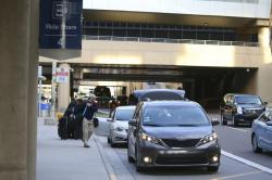 In this Dec. 18, 2019, file photo passengers find their rides at the Ride Share point as they exit Phoenix Sky Harbor International Airport in Phoenix