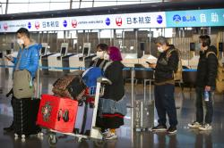 Travelers wearing face masks line up near the Japan Airlines check-in counters at Beijing Capital International Airport in Beijing.