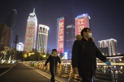 In this Friday, Jan. 31, 2020, photo released by China's Xinhua News Agency, people wearing face masks walk past buildings lit up with slogans of encouragement in Wuhan in central China's Hubei Province.