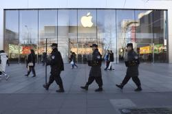 In this March 6, 2019, file photo, Chinese security guards march past an Apple store in Beijing, China