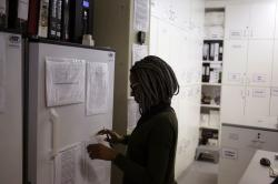 Pharmacist Mary Chindanyika looks at documents on a fridge containing a trial vaccine against HIV on the outskirts of Cape Town, South Africa.