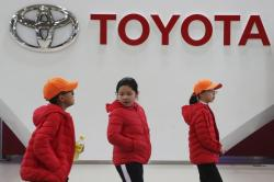 In this Jan. 15, 2020, photo, visitors walk at Toyota gallery in Tokyo. Japanese automaker Toyota Motor Corp. said Friday, Feb. 7, 2020 that it was extending a production stoppage at its plants in China by an extra week, to Feb. 16 due to the outbreak of a virus