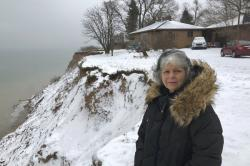 In this Jan. 14, 2020, photo, Rita Alton stands next to her house on the edge of a cliff overlooking Lake Michigan near Manistee, Mich.