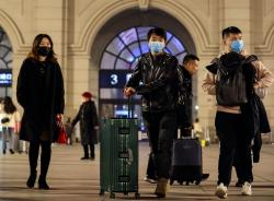 In this Jan. 21, 2020, photo, passengers wearing protective masks walk outside Hankou Railway Station in Wuhan in central China