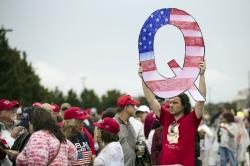 In this Aug. 2, 2018, file photo, David Reinert holding a Q sign waits in line with others to enter a campaign rally with President Donald Trump in Wilkes-Barre, Pa.