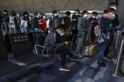 Masked passengers line up to board a flight for Beijing at the airport in Hong Kong.