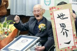 Chitetsu Watanabe, 112, poses next to the calligraphy he wrote after being awarded as the world's oldest living male by Guinness World Records, in Joetsu, Niigata prefecture, northern Japan.