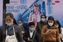 People wearing protective face masks walk on a street in the Central, the business district of Hong Kong.